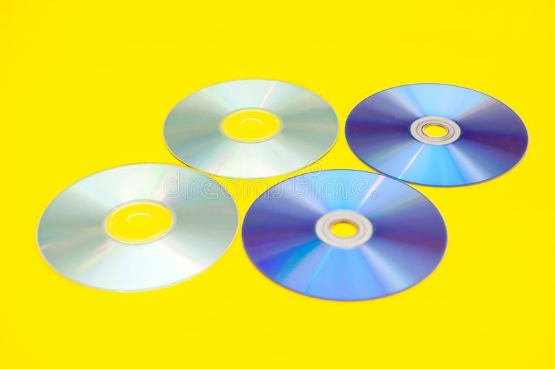 CDs, DVDs,. On a yellow background royalty free stock photos