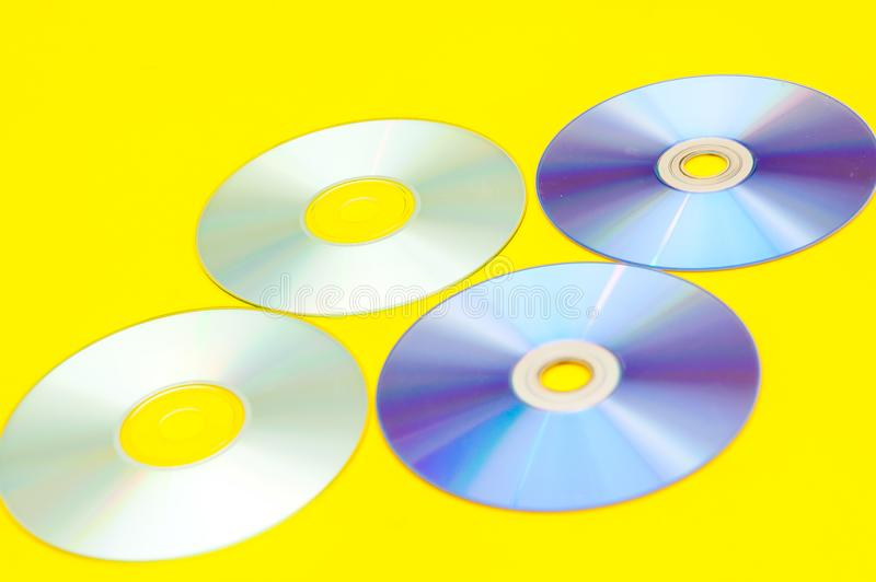 CDs, DVDs,. On a yellow background royalty free stock photo