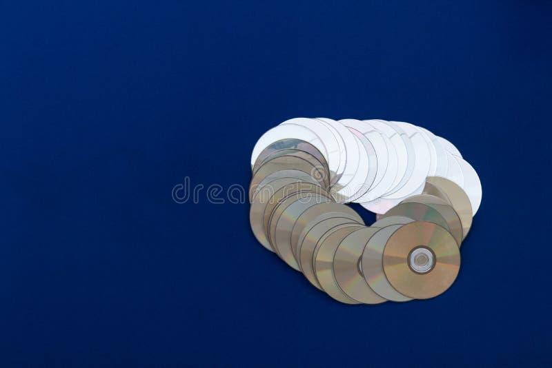CDs overlap on blue cloth. stock photos