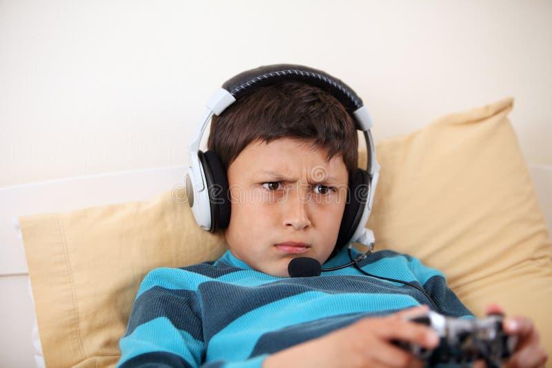 Ceños fruncidos jovenes del muchacho mientras que juega al videojuego imágenes de archivo libres de regalías