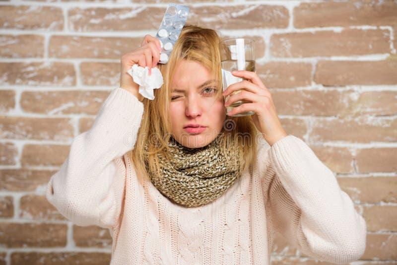 Ce qui à savoir casser la fièvre La femme a ébouriffé l'eau en verre de prise d'écharpe de cheveux et marque sur tablette la bour photos stock