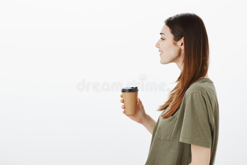 Ce qui peut être meilleur ce café Profilez le portrait de studio de la jeune amie moderne attirante avec le large sourire, se ten photo libre de droits