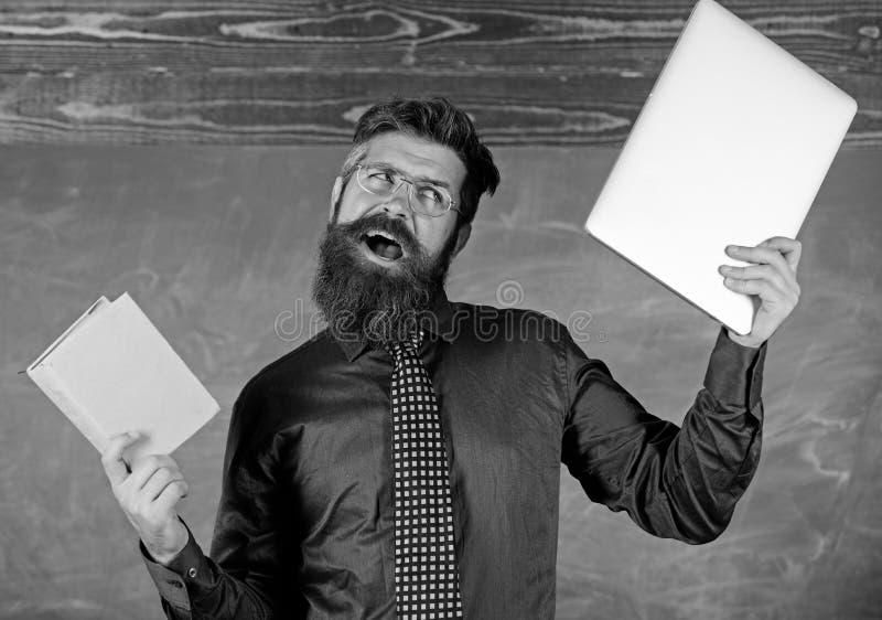 Ce qui vous préférerait Le hippie barbu de professeur tient le livre et l'ordinateur portable Professeur choisissant l'approche m image stock