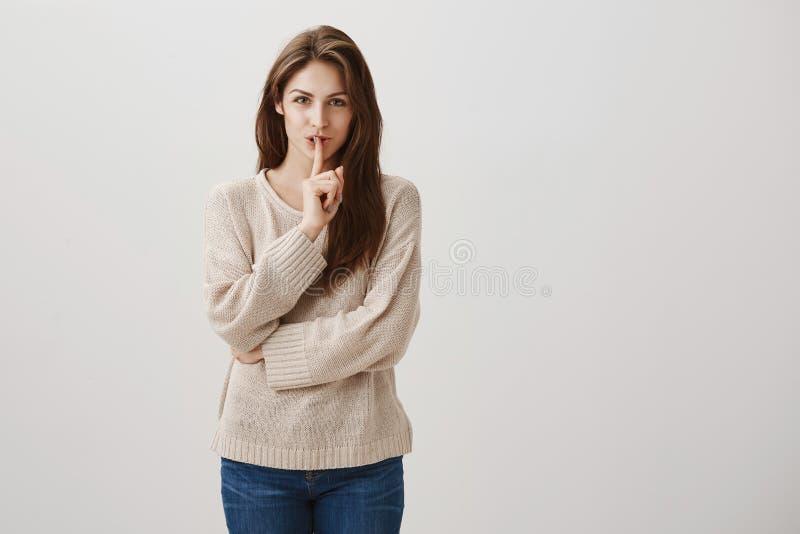 Ce sera notre petit secret Le studio a tiré de la fille caucasienne avec du charme avec de longs cheveux de brune souriant avec l images stock