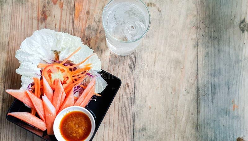 Ceab med kinesisk kål och wasabissås i svart skål på träbord royaltyfri fotografi