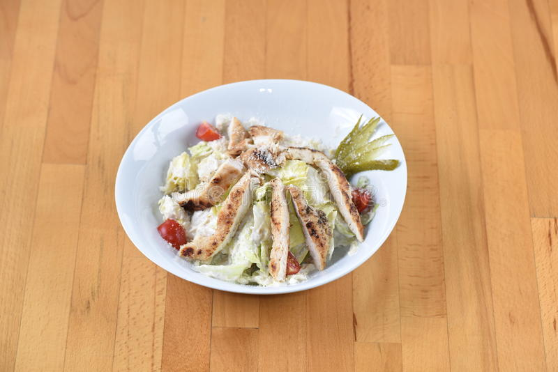 Ceasar Salad with Chicken. Served with tomato and pickles stock photo