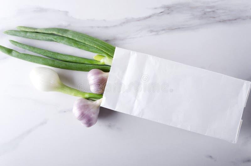 Cebolas e alho frescos da mola no saco de papel branco na superfície de mármore fotos de stock royalty free