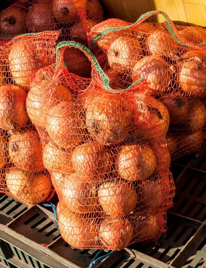Cebolas em uns sacos da malha no mercado imagens de stock