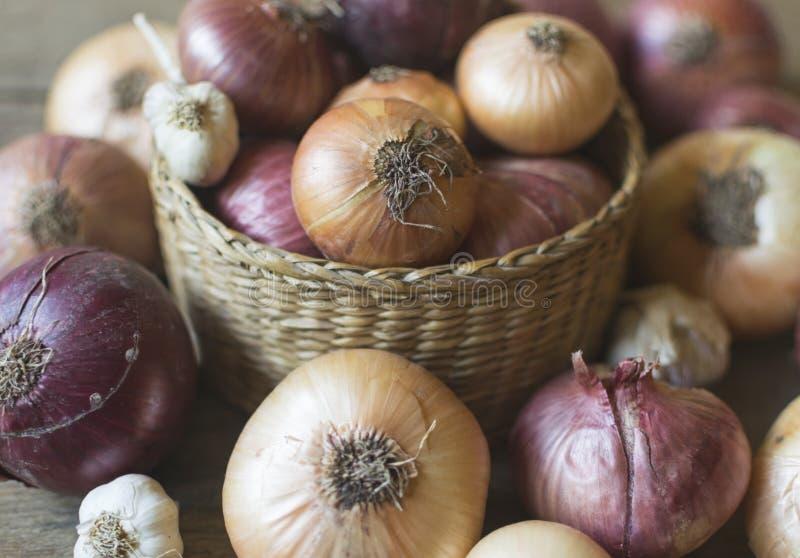 Cebolas, frescas e orgânicas, no cesto e sobre mesa de madeira foto de stock royalty free