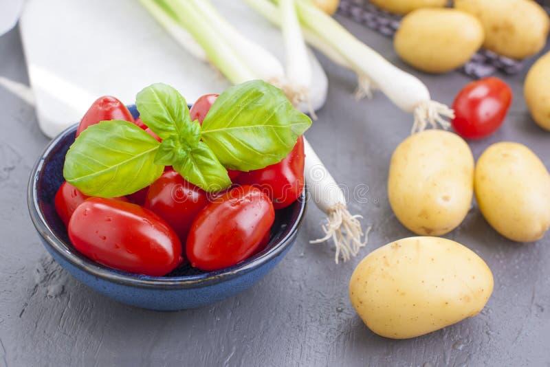 Cebolas verdes frescas, batatas novas, tomates de cereja e manjericão verde alimento e vitaminas saudáveis Vegetais sazonais do v foto de stock