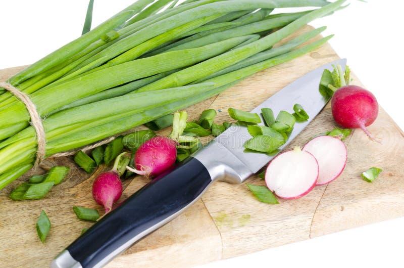 Cebolas verdes frescas, rabanete vermelho na placa de corte fotografia de stock
