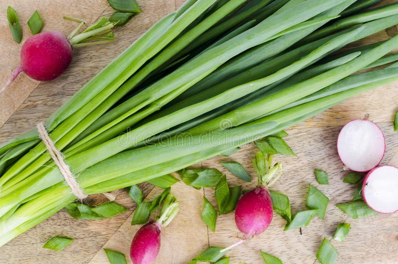 Cebolas verdes frescas, rabanete vermelho na placa de corte foto de stock royalty free