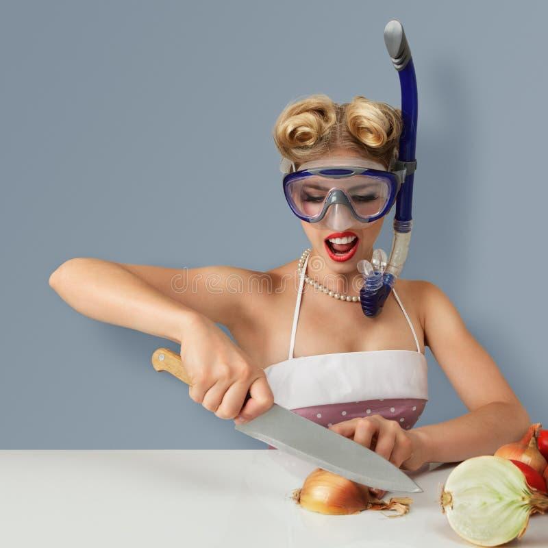 Cebolla del corte de la mujer joven en máscara del salto foto de archivo