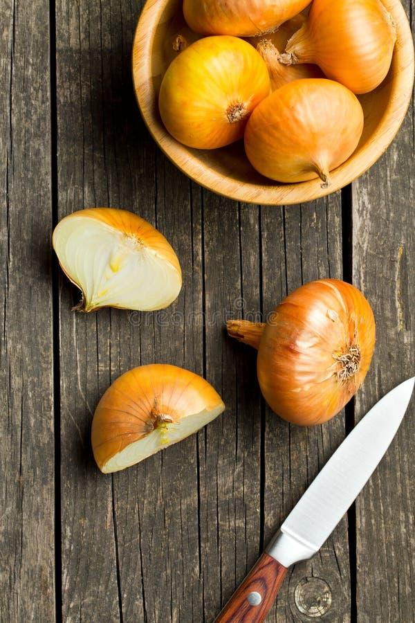 Cebolla fresca partida en dos en la tabla de madera foto de archivo