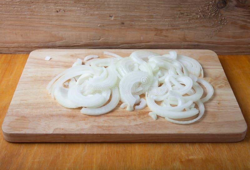 Cebolla fresca tajada en una tabla de cortar de madera ligera en un wo viejo imagen de archivo