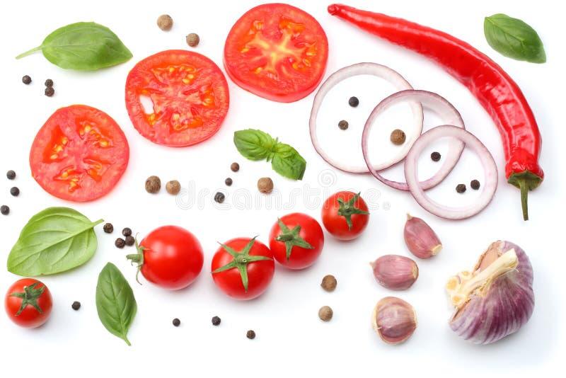 cebolla roja cortada, pimienta de chile candente, tomate, ajo y especias aislados en el fondo blanco Visión superior imagen de archivo