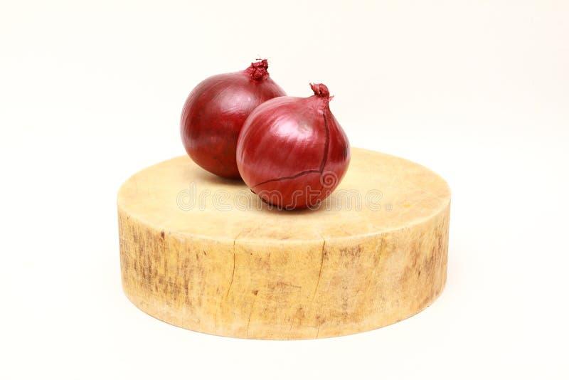 Cebolla roja dos en tabla de cortar de madera tradicional asiática foto de archivo libre de regalías