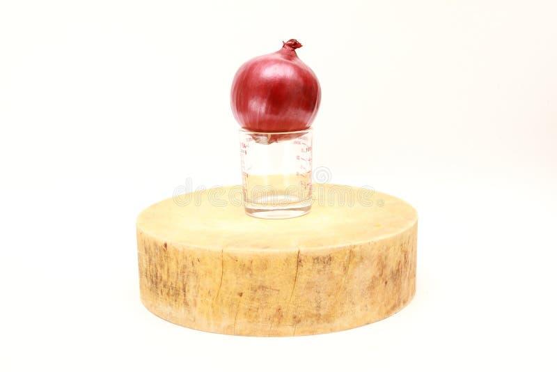 Cebolla roja en la taza de medición en tabla de cortar de madera tradicional asiática imagen de archivo libre de regalías