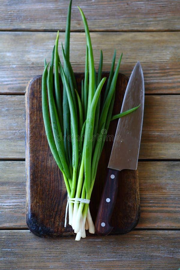 Cebolla verde y cuchillo en tabla de cortar imagenes de archivo