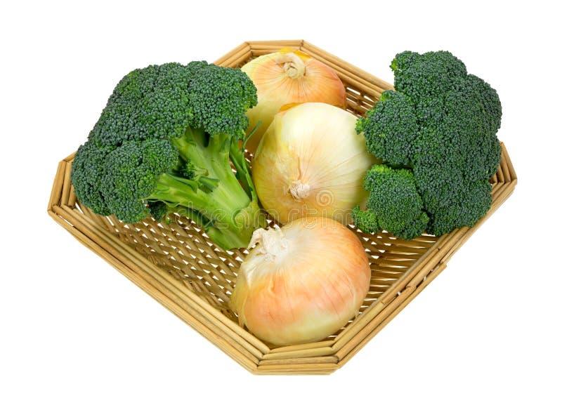 Cebollas de los floretes del bróculi en lado de la cesta imagen de archivo libre de regalías