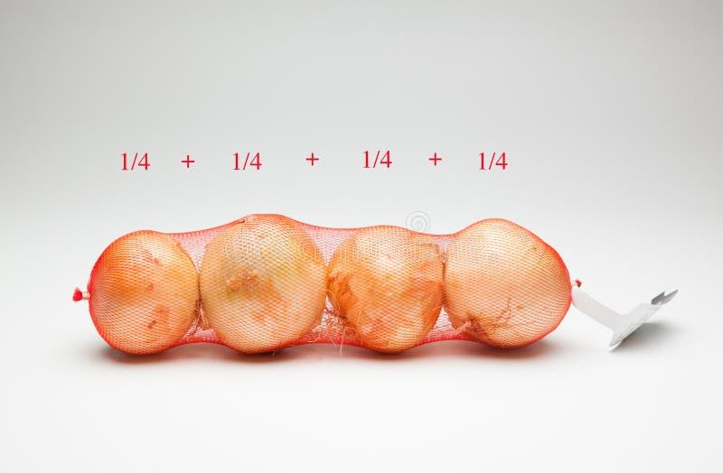 Cebollas en un bolso de la malla fotografía de archivo