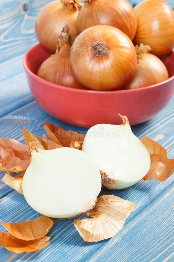 Cebollas frescas peladas y sin pelar en los tableros azules, concepto sano de la nutrición imagen de archivo libre de regalías