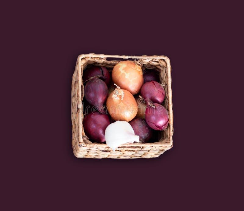 Cebollas púrpuras y blancas en la caja squar, de mimbre aislada en fondo de Burdeos fotos de archivo
