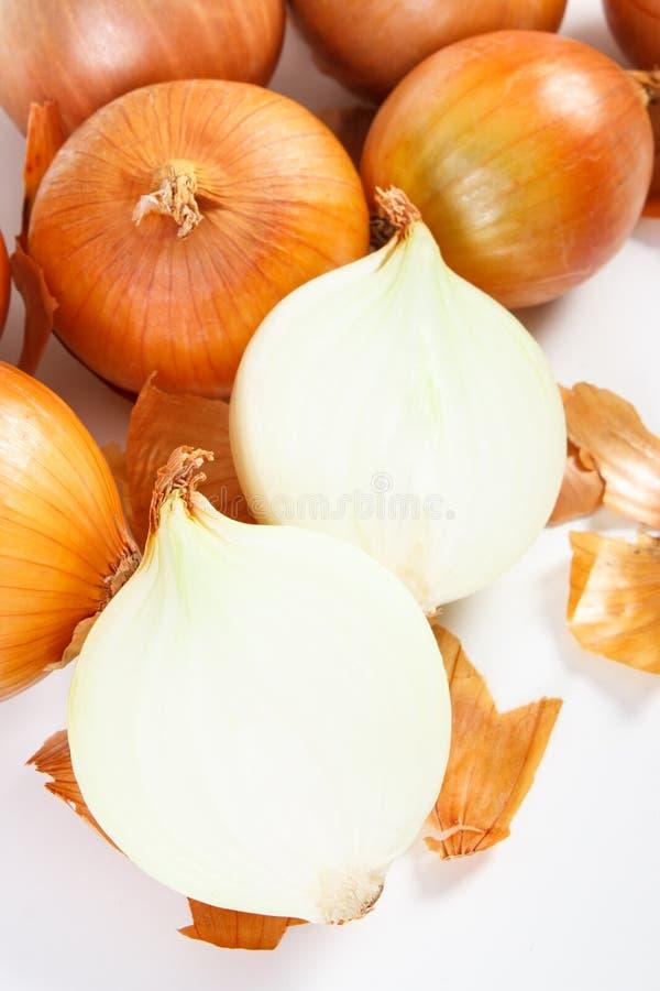 Cebollas peladas y sin pelar en el fondo blanco, de la nutrición sana fotos de archivo