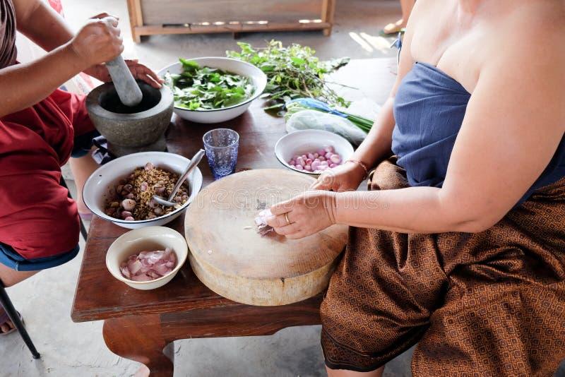 Cebollas rojas cortadas mujer tailandesa en tabla de cortar fotos de archivo libres de regalías