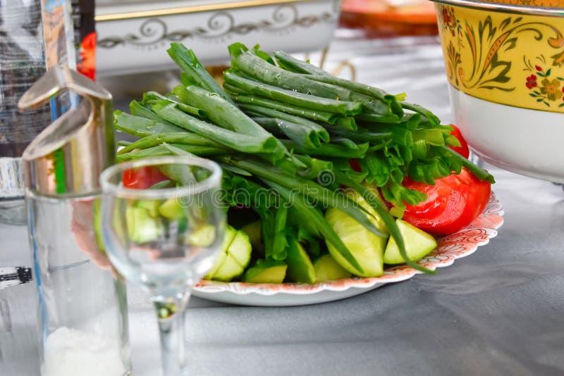Cebollas verdes, pepinos y tomates en un cierre del plato para arriba imagenes de archivo