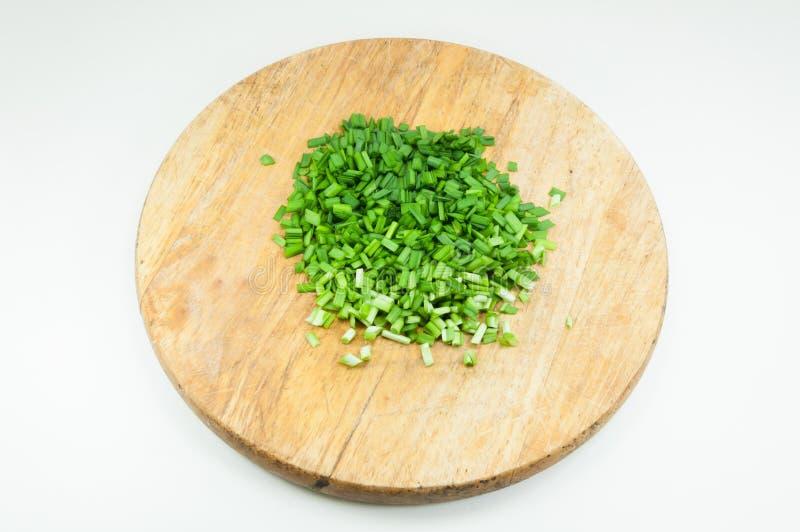 Cebollas verdes tajadas en una tajadera de madera imágenes de archivo libres de regalías