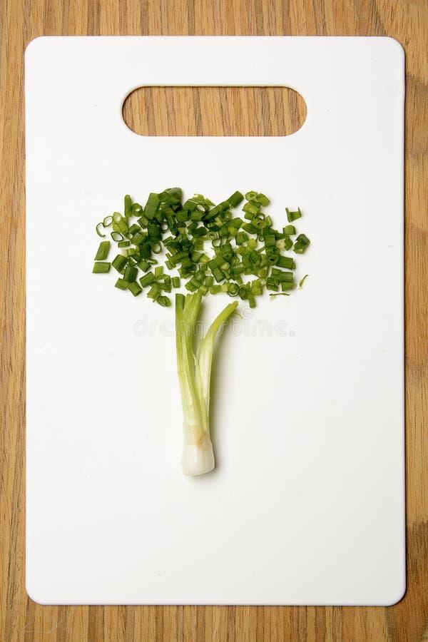 Cebolletas de la cebolla verde en la tabla de cortar imágenes de archivo libres de regalías