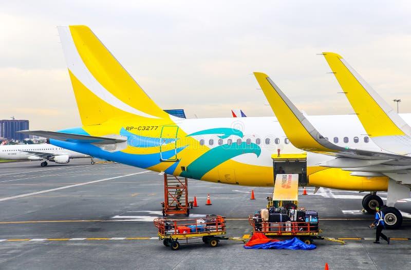 Cebu pacific aircraft at manila airport. Cebu pacific airplane being prepared for flight with cargo loading at ninoy aquino international airport, manila royalty free stock image