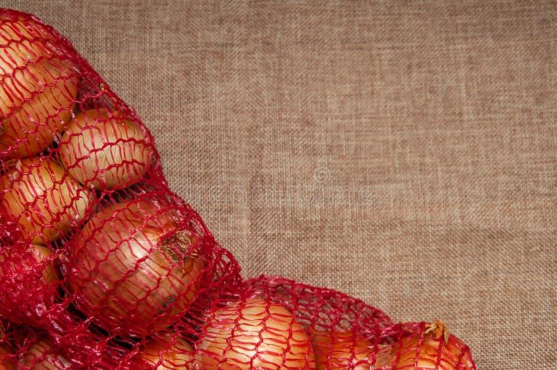 Cebula w czerwonej siatce pakuje na tkaninie zdjęcia stock