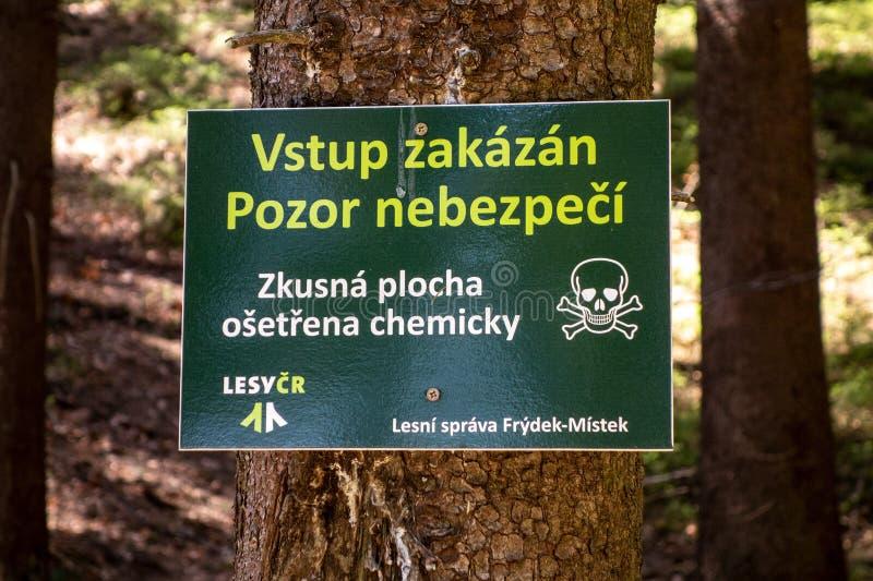 Cechi segnale di pericolo dentro una foresta che nota i pericoli del trattamento chimico fotografia stock libera da diritti