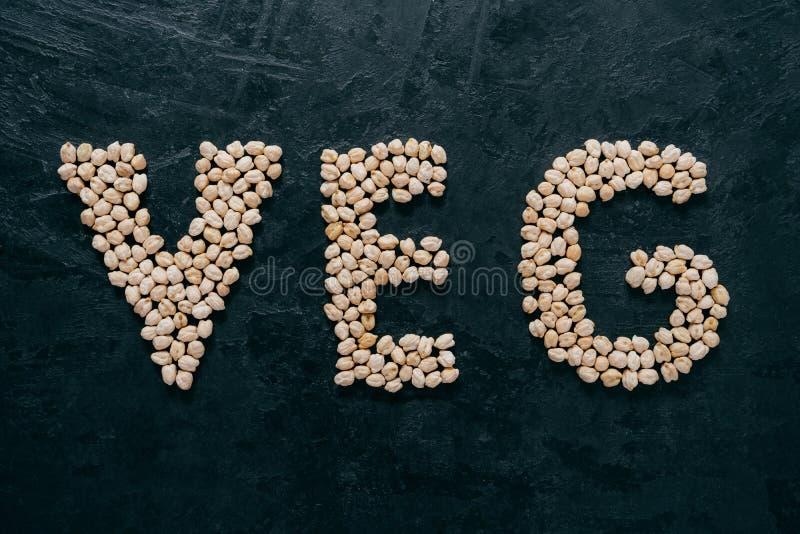 Ceci crudi a forma di nel veg delle lettere, isolato sopra fondo scuro Vegetarianismo e concetto sano di cibo Sano immagine stock