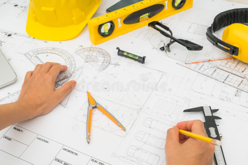 Ceda planos da construção com a ferramenta amarela do capacete e de desenho fotografia de stock