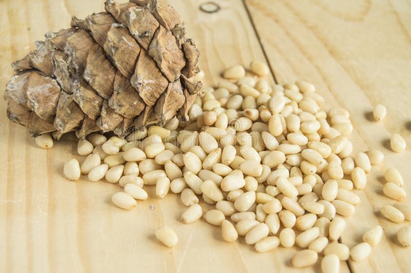 cedar cone with nuts scattered on a light wooden background, organic food and vegetarianism royalty free stock image