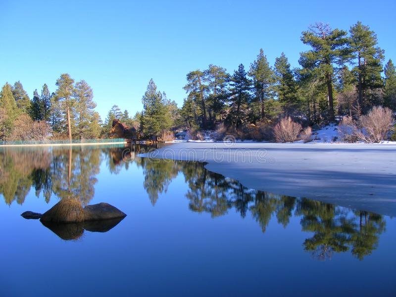 CEDAR LAKE IN THE WINTER. This is a small picturesque lake in the San Bernardino mountains in California. The lake was like a mirror that day and the reflections stock image