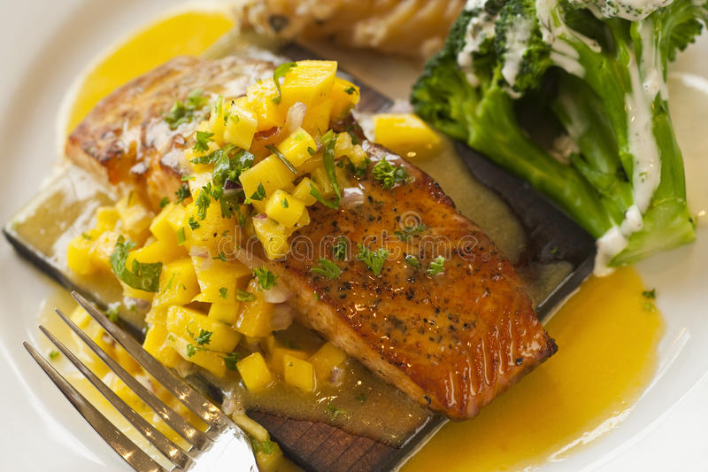 Cedar plank cooked salmon. With mango salsa, Restaurant Jane, Santa Barbara, California, United States of America royalty free stock photography