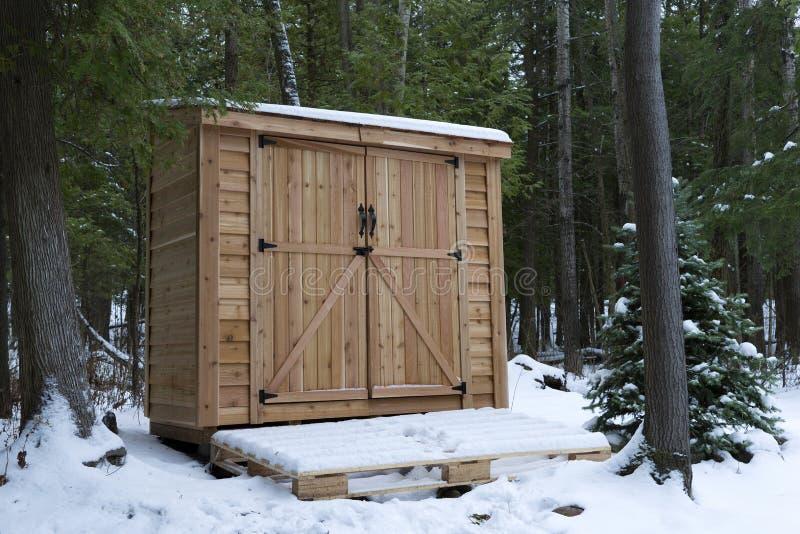 Cedar Storage Shed occidentale nella foresta di inverno fotografia stock