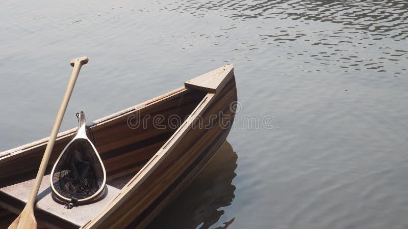 Cedar Strip Canoe auf See mit Ruder und Fischernetz stockbild