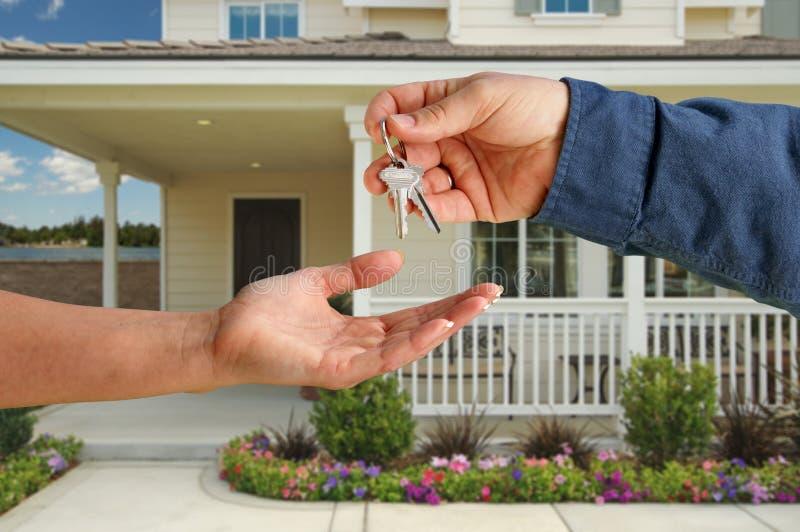 Cedendo as chaves da casa na frente da HOME nova foto de stock royalty free