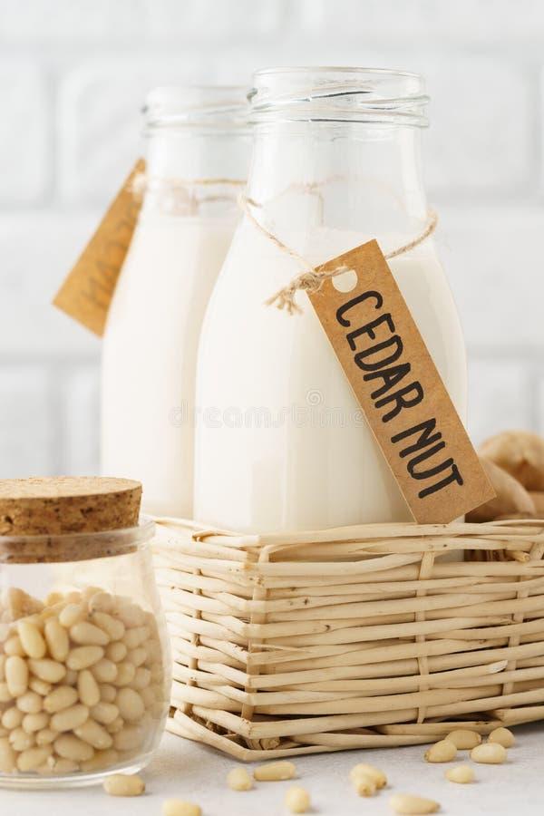 Cederträmuttern mjölkar i en flaska med etiketten och rå ingredienser arkivbild