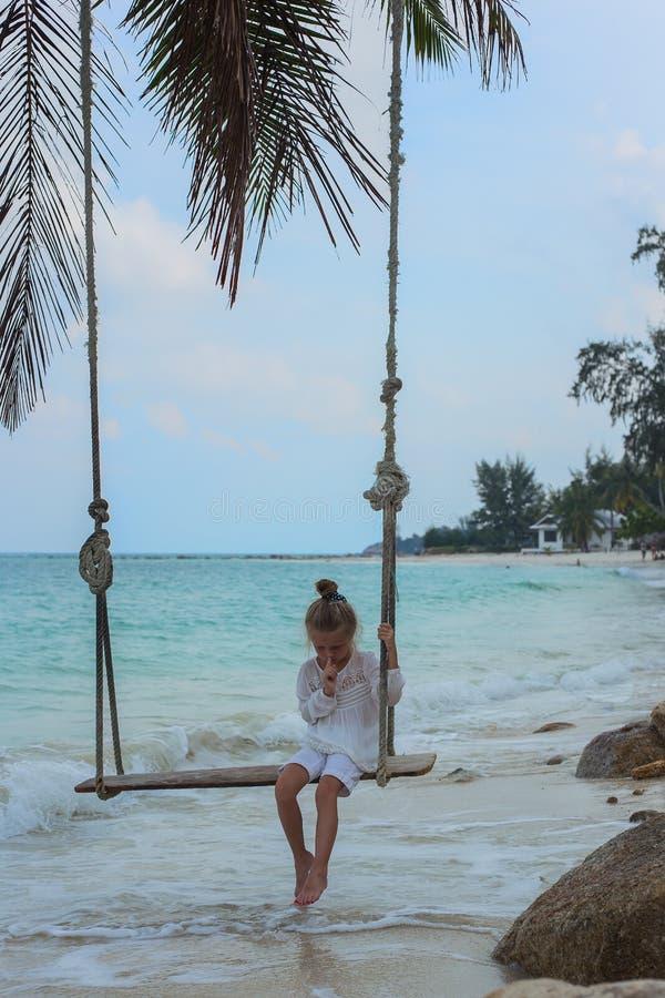 Cedo na manhã a menina no vestido branco que balança no balanço na praia profundamente no pensamento fotos de stock royalty free