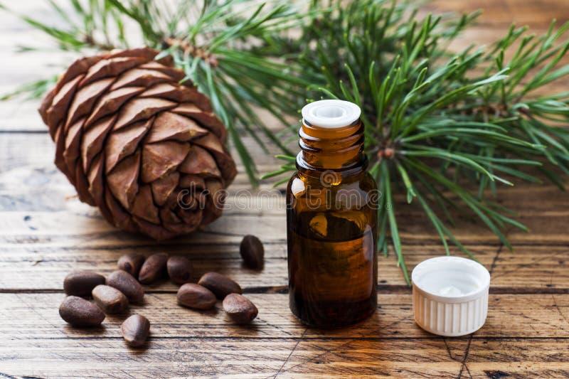 Cedro y aceite esencial de la picea en pequeñas botellas de cristal en fondo de madera Foco selectivo imagenes de archivo