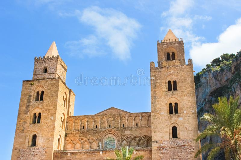 Cefalu Cathedral in Sicily, Italy with blue sky and rocks behind. Famous Roman Catholic basilica erected in Norman style stock photography
