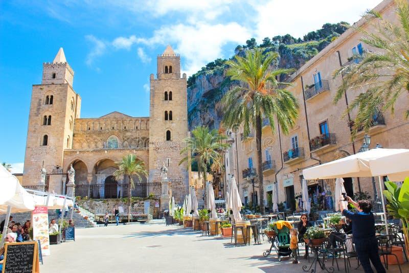 Cefalu, Sicilia, Italia - 7 de abril de 2019: Turistas en la vieja plaza en los jardines al aire libre del caf? delante de la cat imagen de archivo