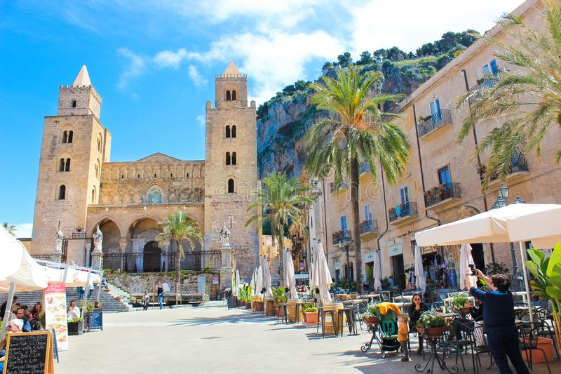 Cefalu, Sicily W?ochy, Apr, - 7th 2019: Tury?ci na starym rynku w plenerowej kawiarni uprawiaj? ogr?dek przed Cefalu katedr? obraz stock
