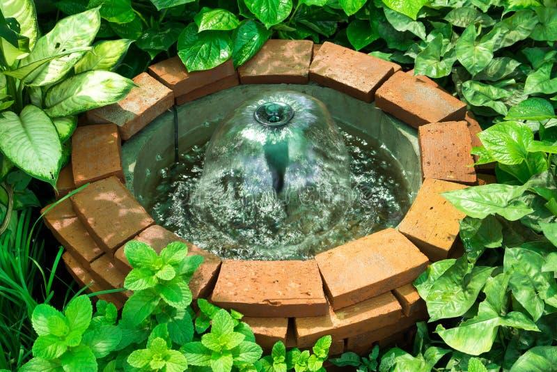 Cegła dobrze z fontanny dekoracją w ogródzie obrazy stock